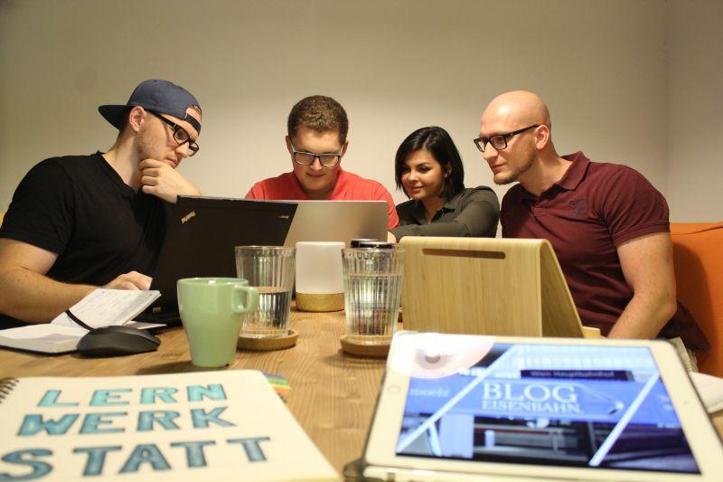 Mein Team und ich sitzen bei Tisch und arbeiten.